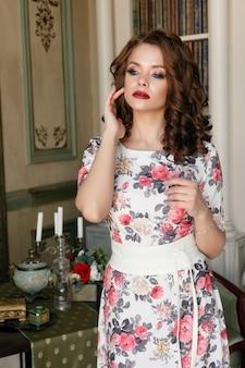 Linda garota linda em vestido de cocktail com flores posando no interior da biblioteca de luxo