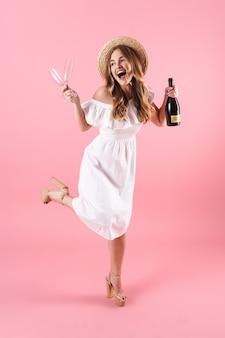 Linda garota loira animada com um vestido de verão em pé, isolada na parede rosa, comemorando com uma garrafa de champanhe e duas taças