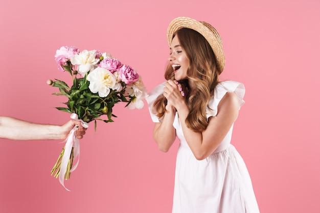 Linda garota loira animada com um vestido de verão em pé, isolada na parede rosa, recebendo um buquê de peônias como um presente