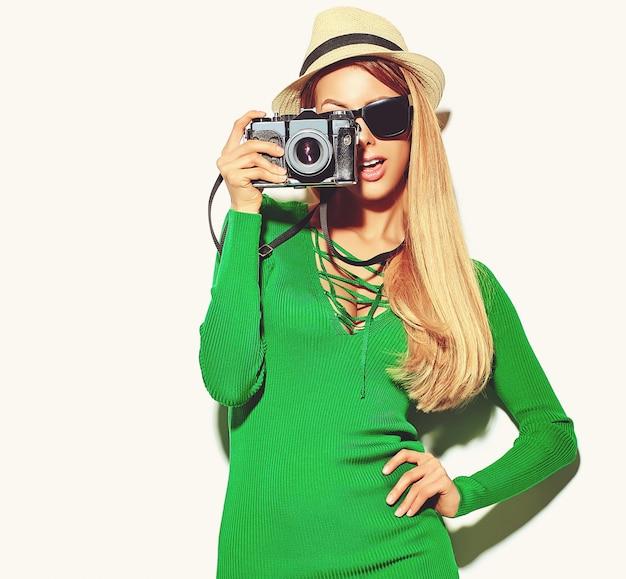 Linda garota loira bonita feliz em roupas de verão casual verde hipster tira fotos segurando a câmera fotográfica retrô,