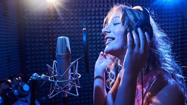Linda garota loira cantando emocionalmente em um estúdio de gravação com microfone e fones de ouvido profissionais, cria um novo álbum de faixas, artista vocal em luz de néon rosa azul, rosto de close-up