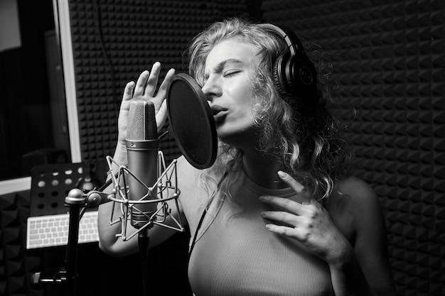 Linda garota loira cantando emocionalmente uma música em um estúdio de gravação com microfone e fones de ouvido profissionais, cria um novo álbum de faixas, um artista vocal em preto e branco, close-up
