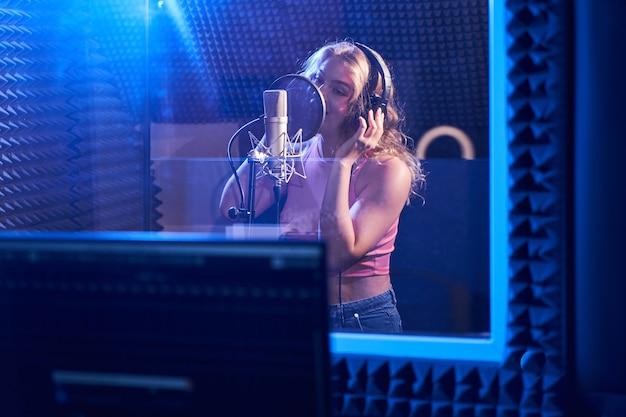Linda garota loira cantando uma música em um estúdio de gravação com microfone e fones de ouvido profissionais, cria um novo álbum de faixas, artista vocal