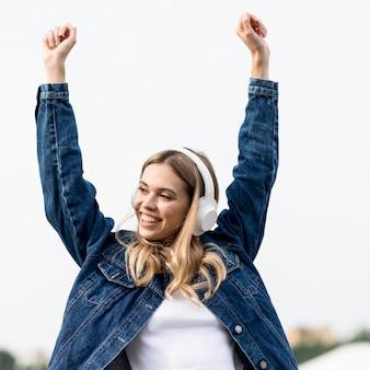 Linda garota loira com as mãos no ar