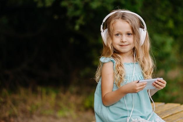 Linda garota loira com fones de ouvido está usando um smartphone e sorrindo enquanto está sentada do lado de fora