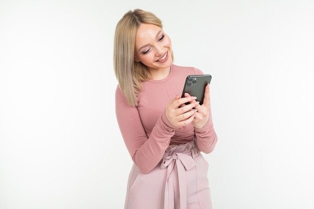 Linda garota loira com um telefone nas mãos dela, sobre um fundo branco, com espaço de cópia
