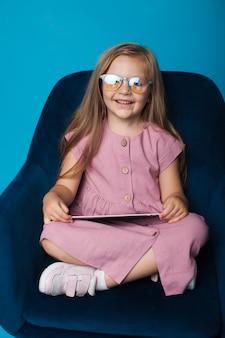 Linda garota loira de óculos brincando com um tablet em uma poltrona em uma parede azul e sorrindo