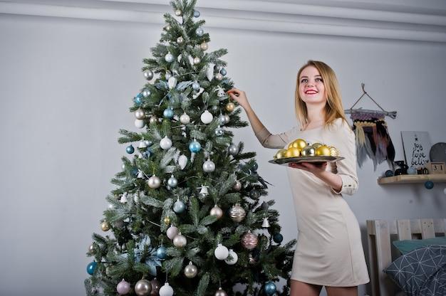 Linda garota loira de vestido bege contra árvore de ano novo com bolas de ouro ano novo no estúdio