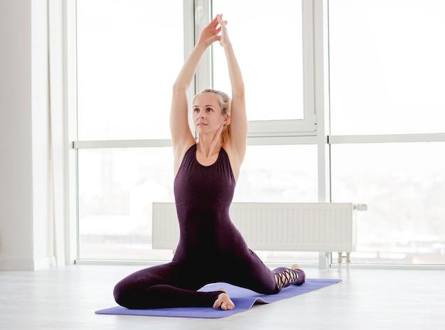 Linda garota loira durante treino de ioga para corpo flexível