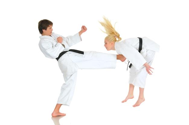 Linda garota loira e um jovem caratê atrevido estão treinando em um quimono. jovem casal de atletas se preparando para uma apresentação.