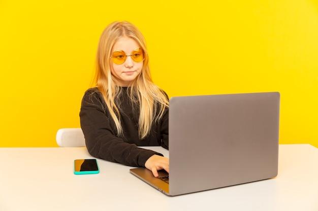 Linda garota loira em casa na frente do laptop fazendo um vídeo para vlog e trabalhando como blogueira