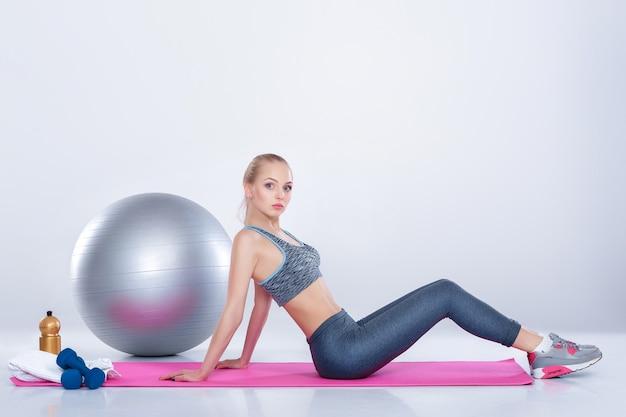 Linda garota loira em roupas esportivas fazendo exercícios em um tapete de fitness em um fundo cinza