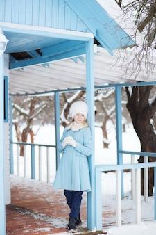 Linda garota loira em um casaco azul e chapéu de pele branca no inverno. tempo nevado. a garota na varanda da casa. casa de inverno. modelo posando na rua. o conceito de férias de inverno.