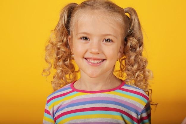 Linda garota loira feliz sorridente em um fundo amarelo com uma jaqueta colorida