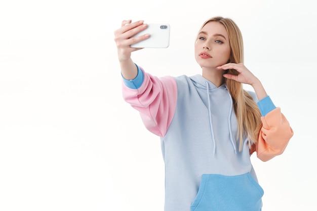 Linda garota loira feminina com expressão sensual, tocando suavemente o rosto enquanto tira uma selfie no celular