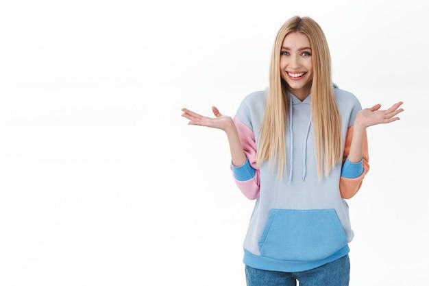 Linda garota loira fofa e boba com um capuz, dando de ombros e espalhando as mãos para os lados, sorrindo e pedindo desculpas