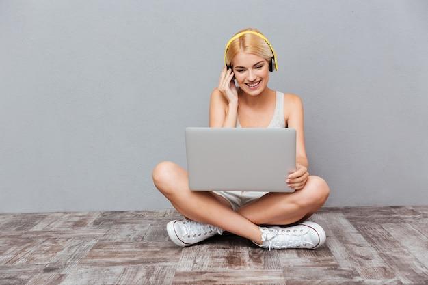 Linda garota loira inteligente com laptop e fones de ouvido isolados na parede cinza