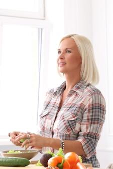 Linda garota loira na cozinha