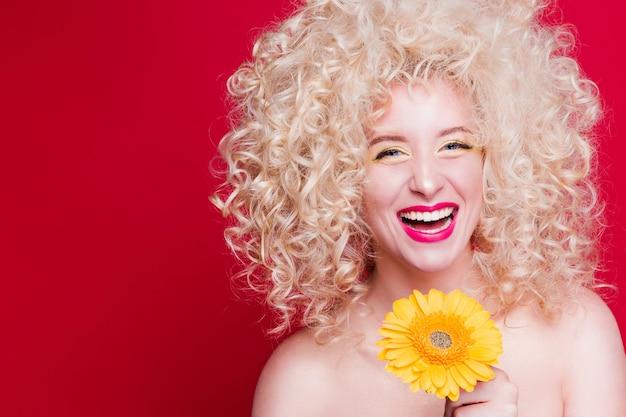 Linda garota loira na moda em estilo retro com penteado encaracolado volumoso