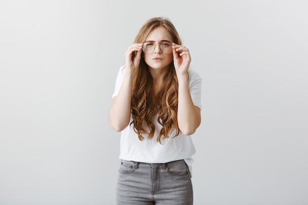 Linda garota loira não consegue ver, apertando os olhos e olhando nos óculos