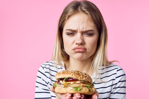 Linda garota loira no estilo de vida de fast-food de close-up de hambúrguer de camiseta listrada. foto de alta qualidade