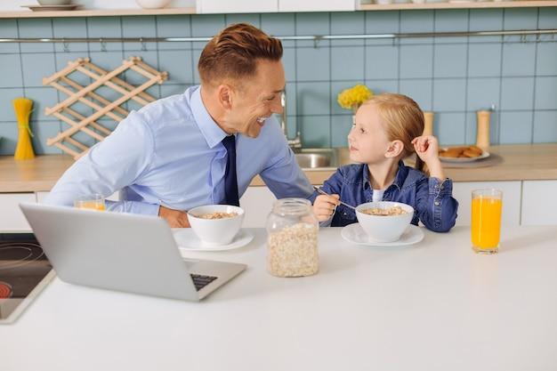 Linda garota loira positiva sentada à mesa da cozinha e olhando para o pai enquanto comia
