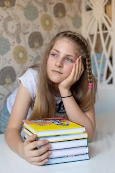 Linda garota loira segura uma pilha de livros coloridos a menina pensou sonhar conceito, lazer, leitura e educação