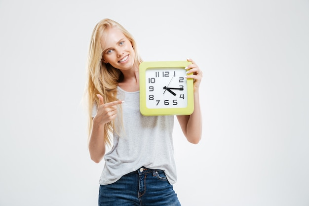 Linda garota loira sorridente apontando o dedo para o relógio de parede isolado em uma parede branca
