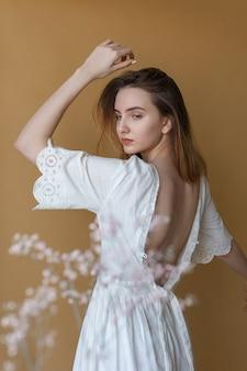 Linda garota magra cabelos longos, vestido branco com as costas nuas, posando em fundo bege