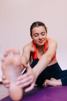Linda garota magra vestida com top esportivo rosa e meia-calça fazendo alongamento no tapete para se exercitar na academia