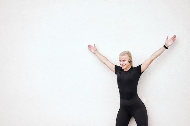 Linda garota magro alegre vestindo roupas esportivas pretas e tênis elegantes brancos, ouvindo música e alongamentos após o treino