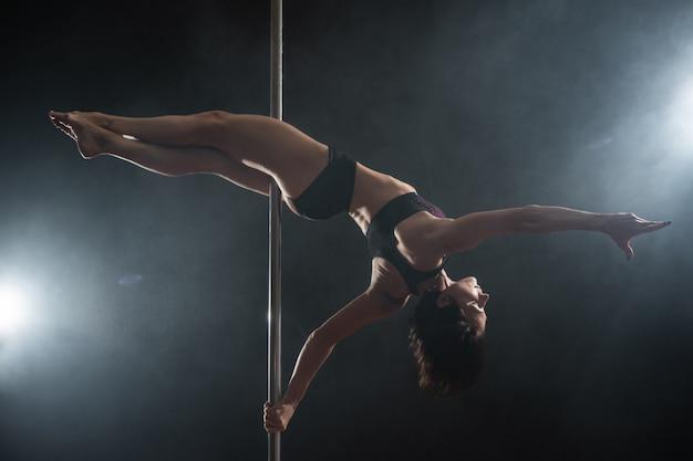 Linda garota magro com pilão. dançarina feminina dançando no preto