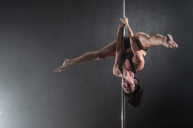Linda garota magro com pilão feminino pole dancer dançando sobre um fundo preto