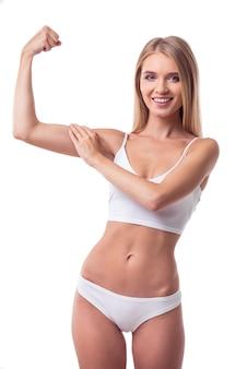 Linda garota magro em lingerie branca está mostrando seus músculos. conceito de dieta