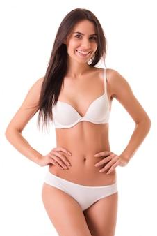 Linda garota magro em lingerie branca está olhando para a câmera.