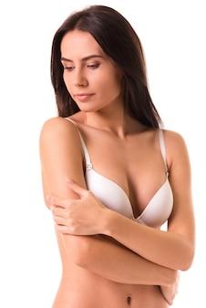 Linda garota magro em lingerie branca está posando para a câmera.