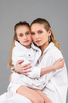 Linda garota mais velha de cabelos escuros carregando sua irmã mais nova e abraçando firmemente com as duas mãos