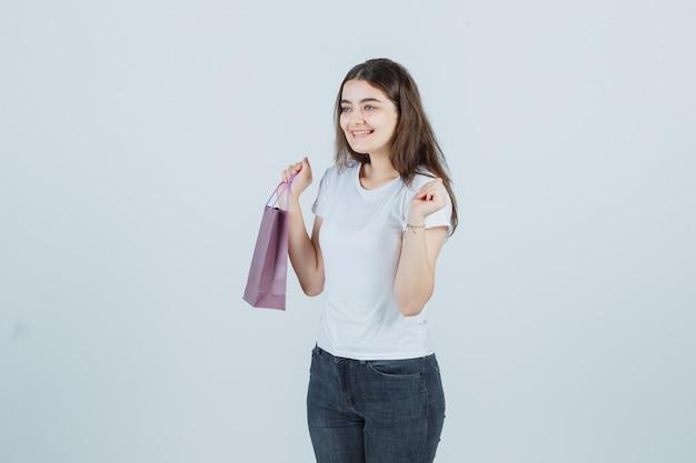 Linda garota mantendo o saco de papel em t-shirt, jeans e parecendo feliz, vista frontal.