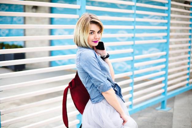 Linda garota meio virada com lábios cor de rosa brilhantes segurando um smartphone com listras azuis e brancas no fundo.