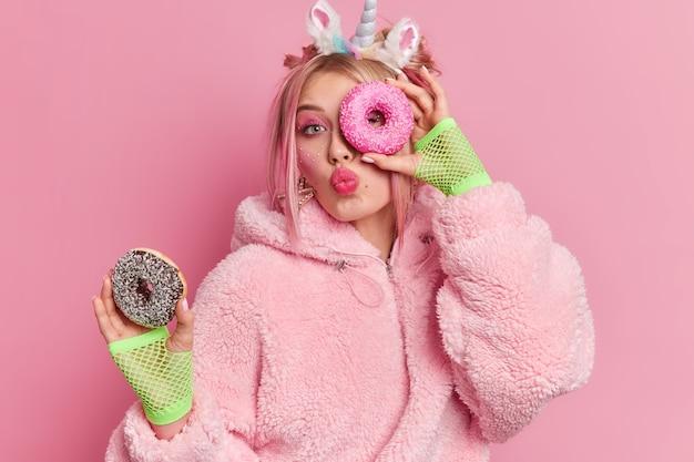 Linda garota milenar com lábios abertos segurando duas rosquinhas doces deliciosas e gostando de comer sobremesa
