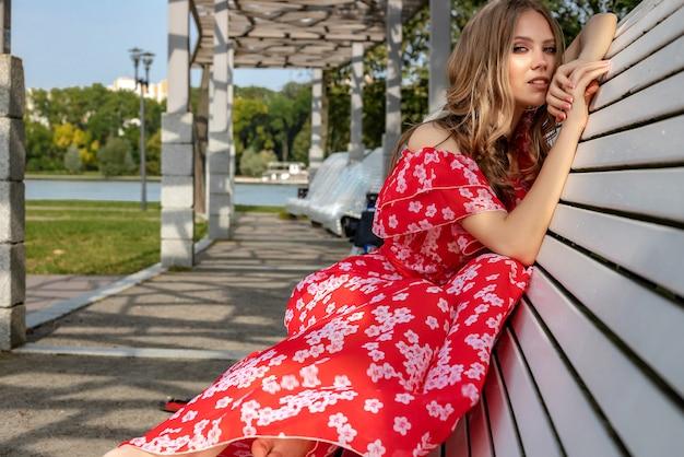 Linda garota, modelo, mulher de cabelos castanhos com cabelos longos em um vestido vermelho, senta-se em um banco e posa com um olhar descontraído e lânguido.