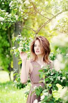 Linda garota modelo no jardim de flores