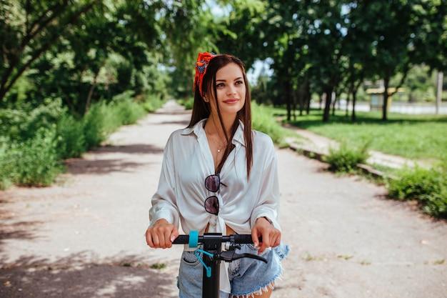 Linda garota morena anda em uma scooter de eletrodo no parque, ela está vestindo uma camisa branca. conceito de eco transporte e aluguel.