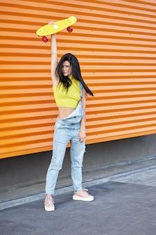 Linda garota morena ativa com cabelos longos, vestindo blusa amarela, macacão jeans azul e tênis rosa elegantes