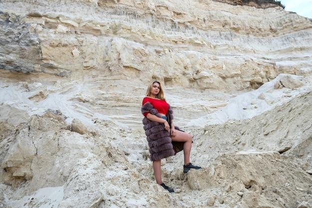 Linda garota morena com camiseta e shorts ocre, casaco de pele, posando em pedras de areia vazias