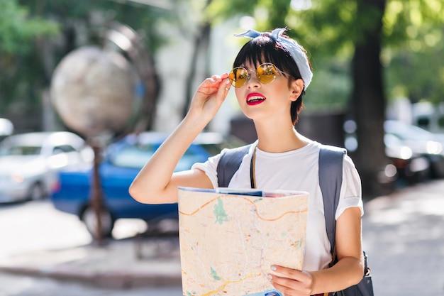 Linda garota morena com roupa vintage segurando o mapa da cidade e olhando para longe com expressão preocupada
