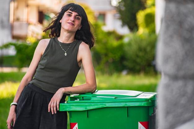 Linda garota morena perto da caçamba de lixo ao ar livre