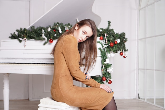 Linda garota morena sensual com cabelos longos e lisos perto de um piano branco com decoração de natal