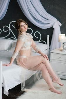 Linda garota morena sexy em cueca branca, posando em uma sala do estúdio interior