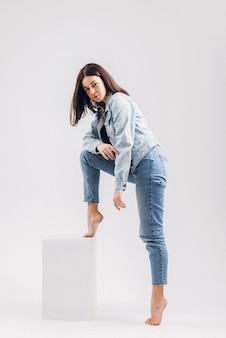 Linda garota morena sexy em jeans e roupa íntima, posando em um fundo branco